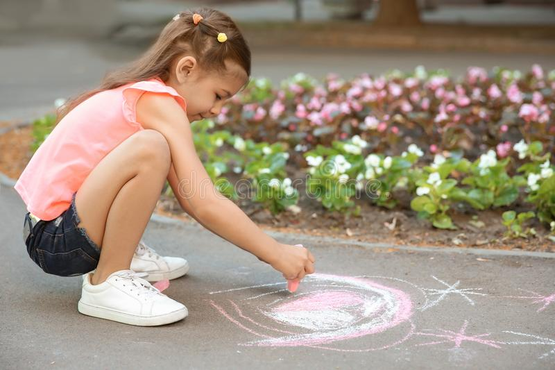 Little child drawing heart with chalk. On asphalt stock photos