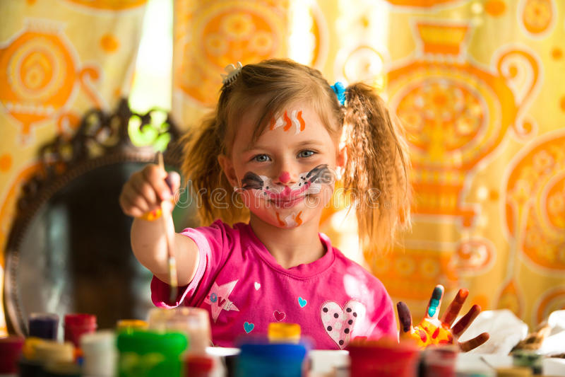 Little child drawing paint with paint of face stock photos