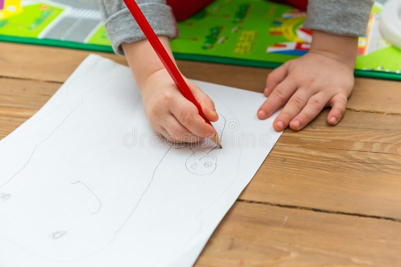Little child drawing with pencil on white paper. Close up of toddler playing on floor vector illustration