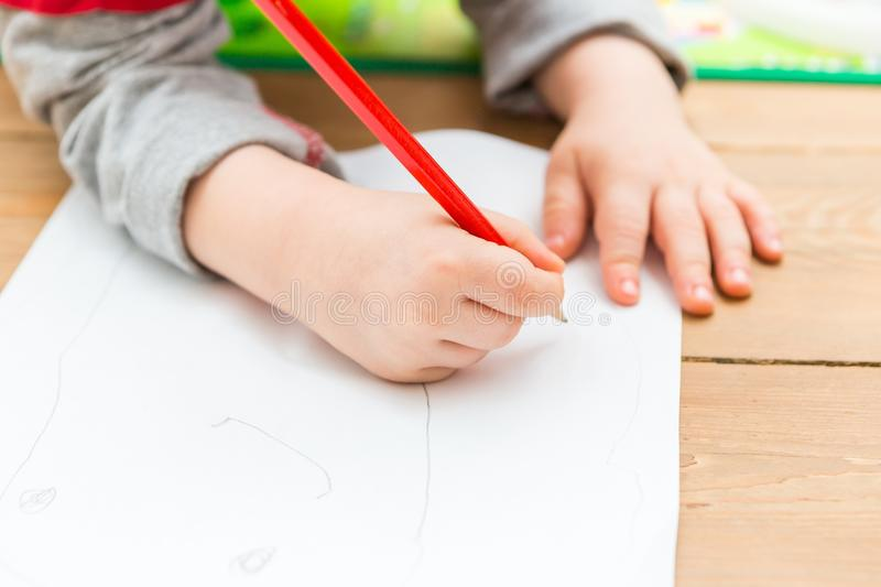 Little child drawing with pencil on white paper. Close up of toddler playing on floor stock illustration