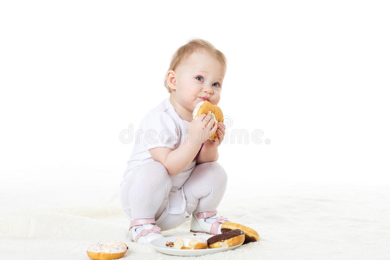 Little child eating doughnuts. stock photo