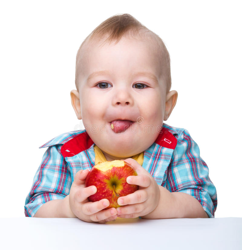 Little child is eating red apple stock photos