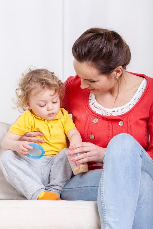 Little child eating snacks stock photos