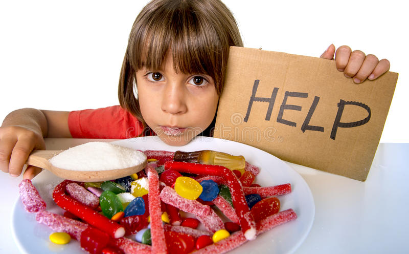 Little child eating sweet sugar in candy dish holding sugar spoo. Sad and vulnerable 4 or 5 years old female child asking for help eating dish full of candy royalty free stock photo