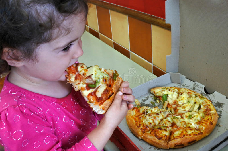 Little Child eats fast food. Little child girl age 2 eats fast food. Children healthcare concept. Real people. Copy space stock photos