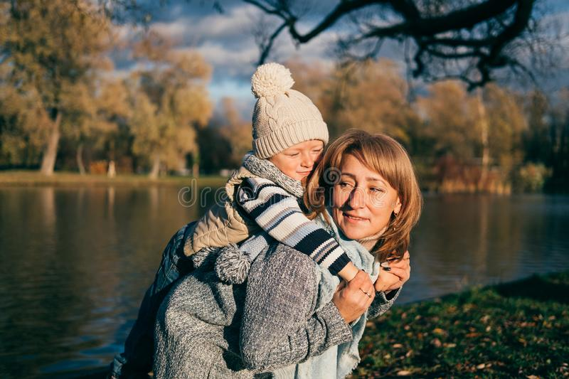 Little child embracing his mom. Family having fun in autumn park outdoors, hugging, laughing, relaxing, enjoy life. Close up sunny royalty free stock photo