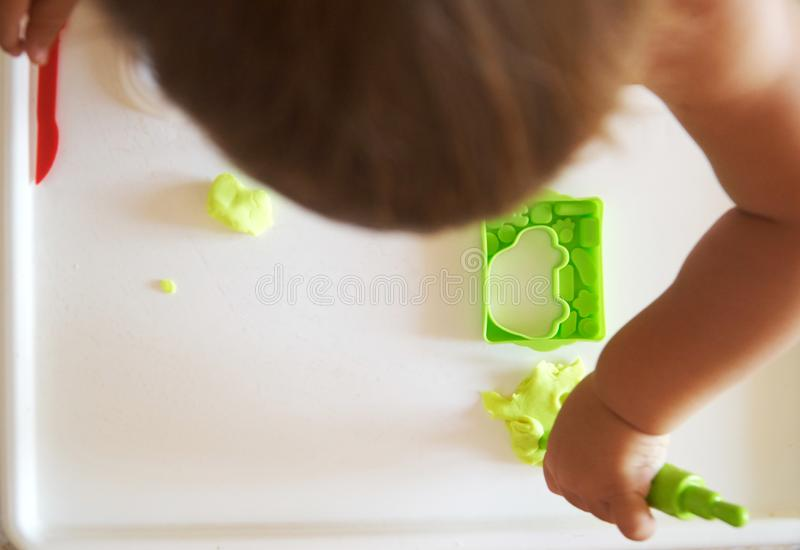 Little child engaged in playdough modeling at table, top view. lifestyle royalty free stock photo