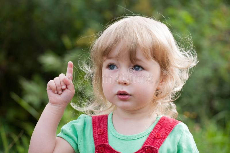 Little child face and index finger pointing up closeup view stock photo