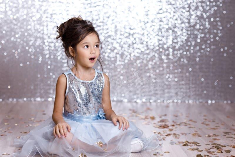 Little girl in blue dress sitting on the floor with confetti. Little child girl in blue dress sitting on the floor with confetti on background with silver bokeh royalty free stock photo