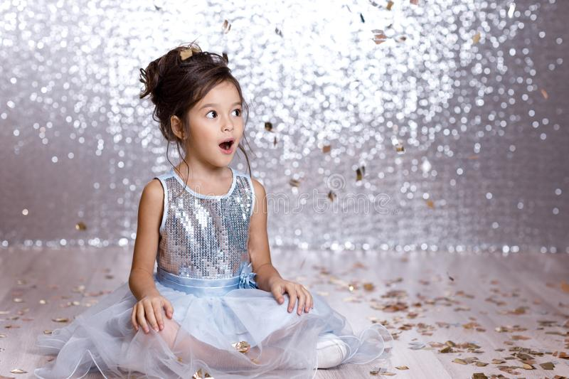 Little girl in blue dress sitting on the floor with confetti. Little child girl in blue dress sitting on the floor with confetti on background with silver bokeh royalty free stock images