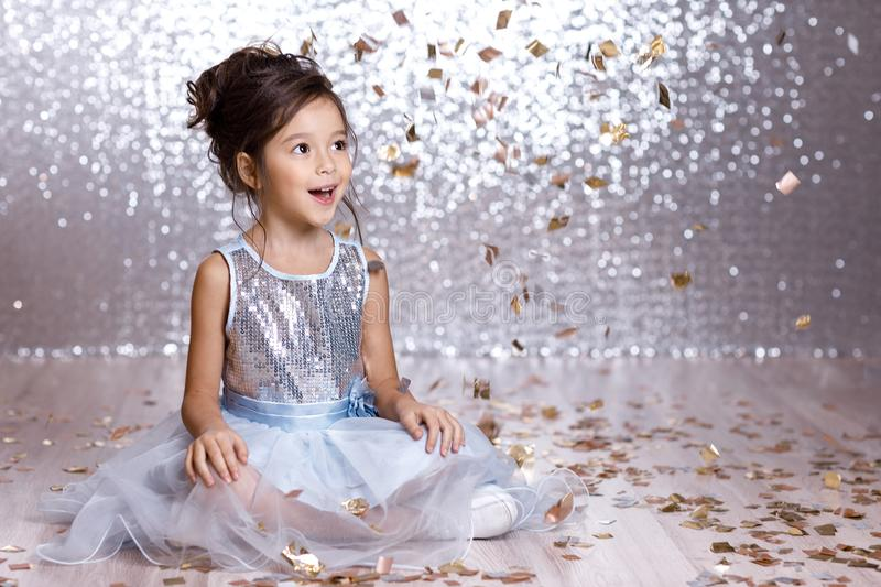 Little girl in blue dress sitting on the floor with confetti. Little child girl in blue dress sitting on the floor with confetti on background with silver bokeh royalty free stock photos
