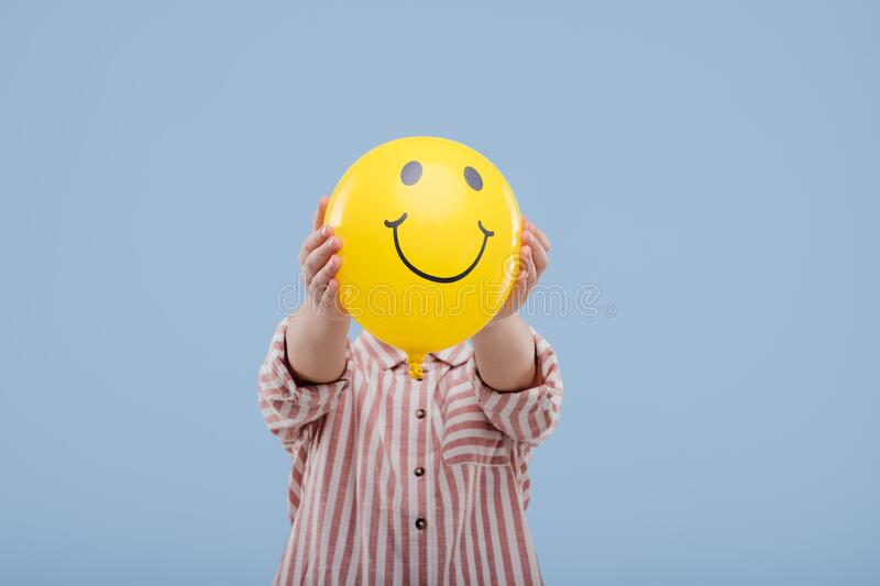 Little child girl covering face with yellow balloon with smile, stock photos