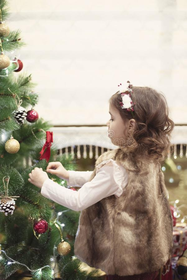Little child girl decorating Christmas tree with balls at home, indoors. Close up. Christmas concept royalty free stock photography