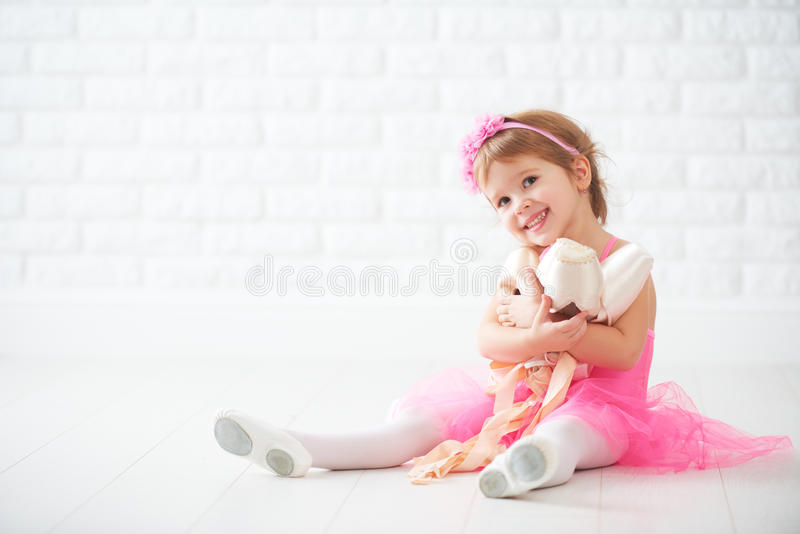 Little child girl dreams of becoming ballerina with ballet shoe stock photos