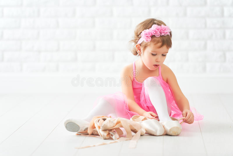 Little child girl dreams of becoming ballerina with ballet shoe. S and pointe shoes in a pink tutu skirt royalty free stock photos