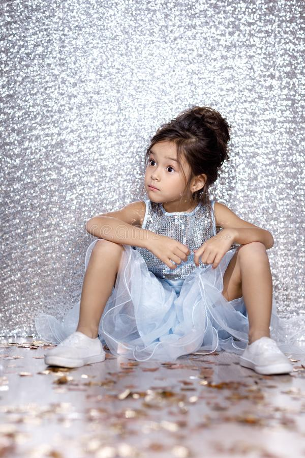 Little child girl in dress sitting on the floor with confetti. Little child girl in blue dress sitting on the floor with confetti on background with silver bokeh stock photography