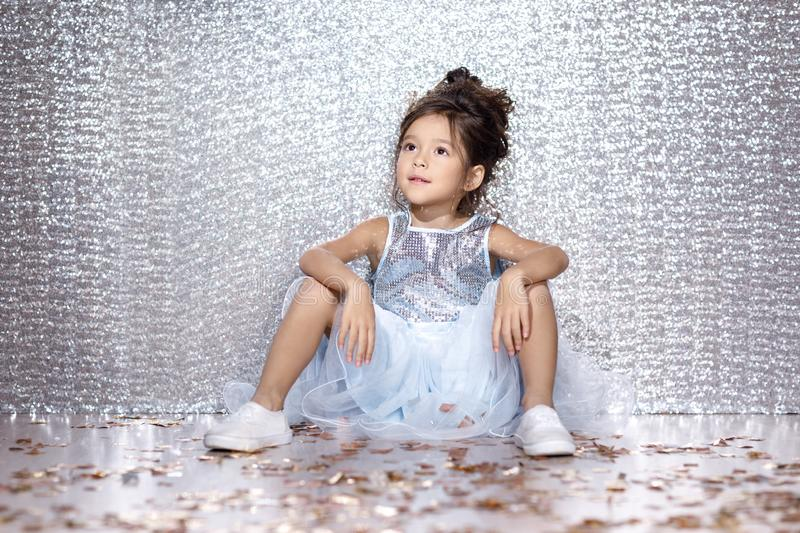 Little child girl in dress sitting on the floor with confetti. Little child girl in blue dress sitting on the floor with confetti on background with silver bokeh stock images