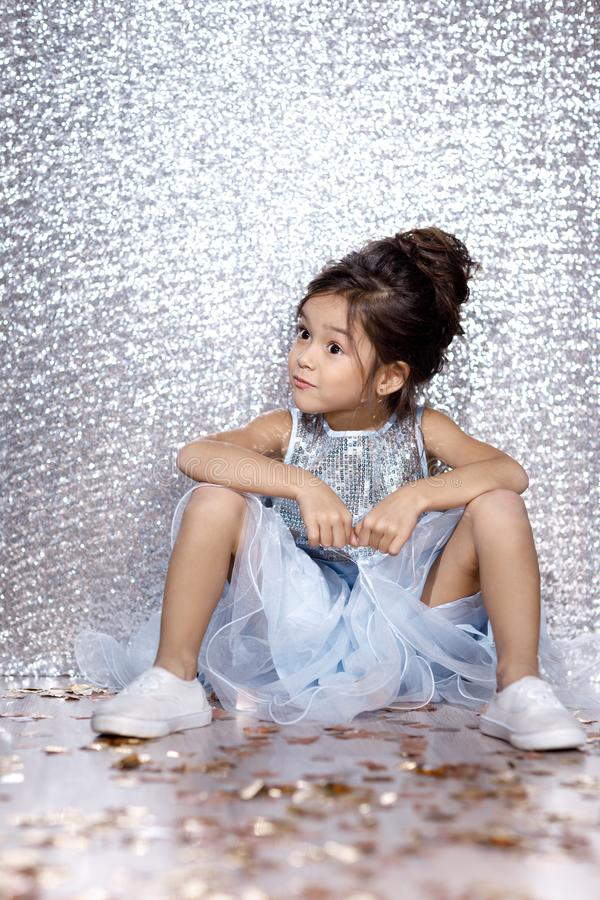 Little child girl in dress sitting on the floor with confetti. Little child girl in blue dress sitting on the floor with confetti on background with silver bokeh royalty free stock photography