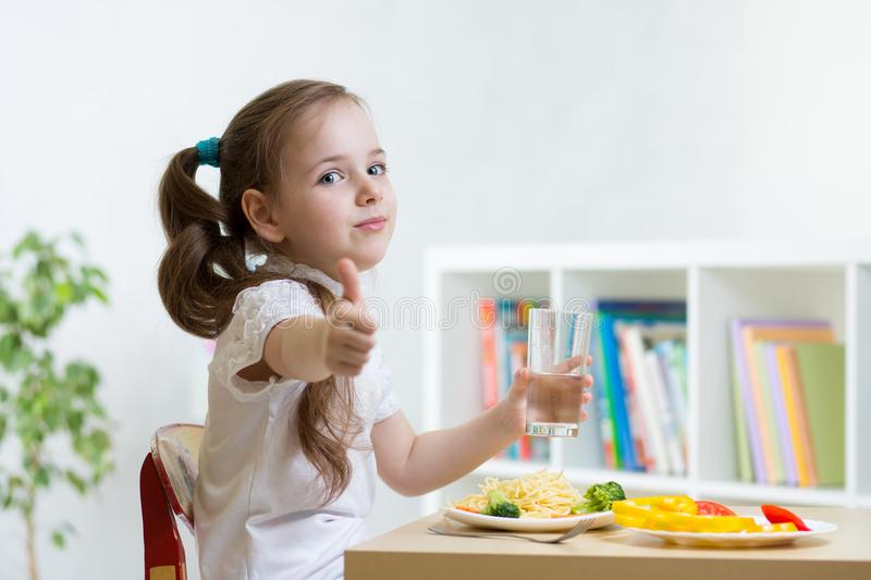 Little girl eating pasta with broccoli, carrot and showing ok hand sign stock photography