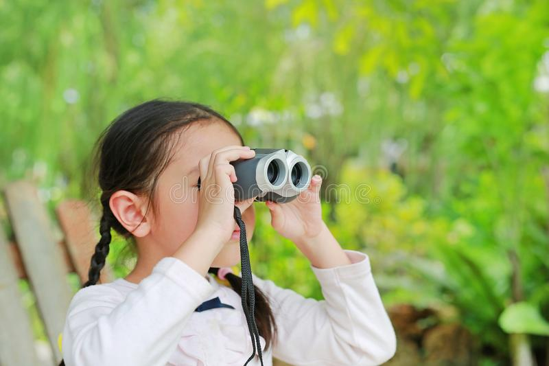 Little child girl in a field looking through binoculars in nature outdoor. Explore and adventure concept.  royalty free stock photo