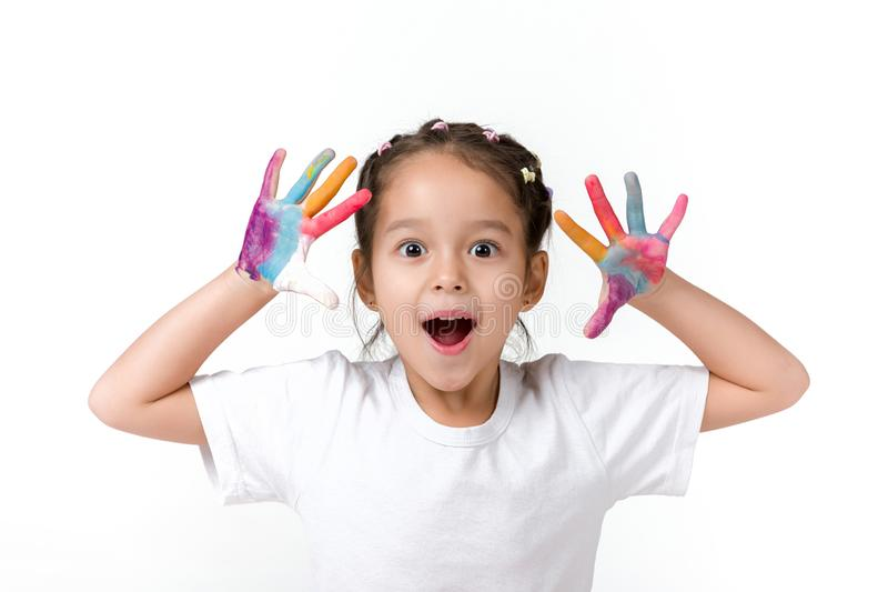 Little child girl with hands painted in colorful paint. Cute surprised little child girl with hands painted in colorful paint isolated on white background royalty free stock photo
