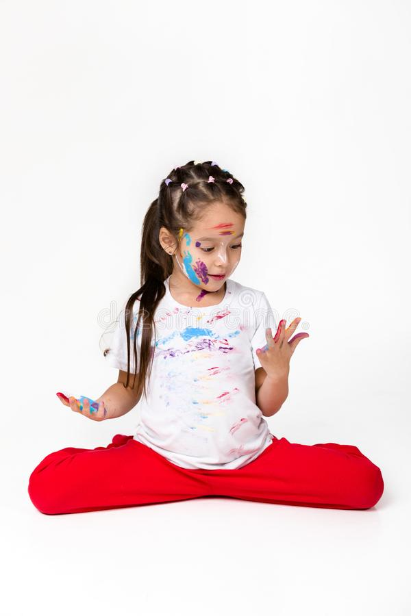 Little child girl with hands painted in colorful paint. Scared little child girl looks at his hands painted in colorful paint isolated on white background stock photography