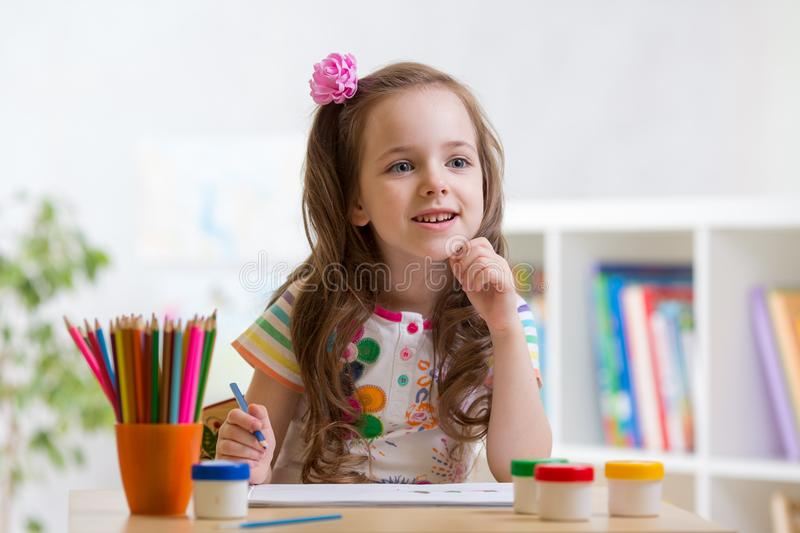 Little child girl with holding colored pencils in living room royalty free stock photo