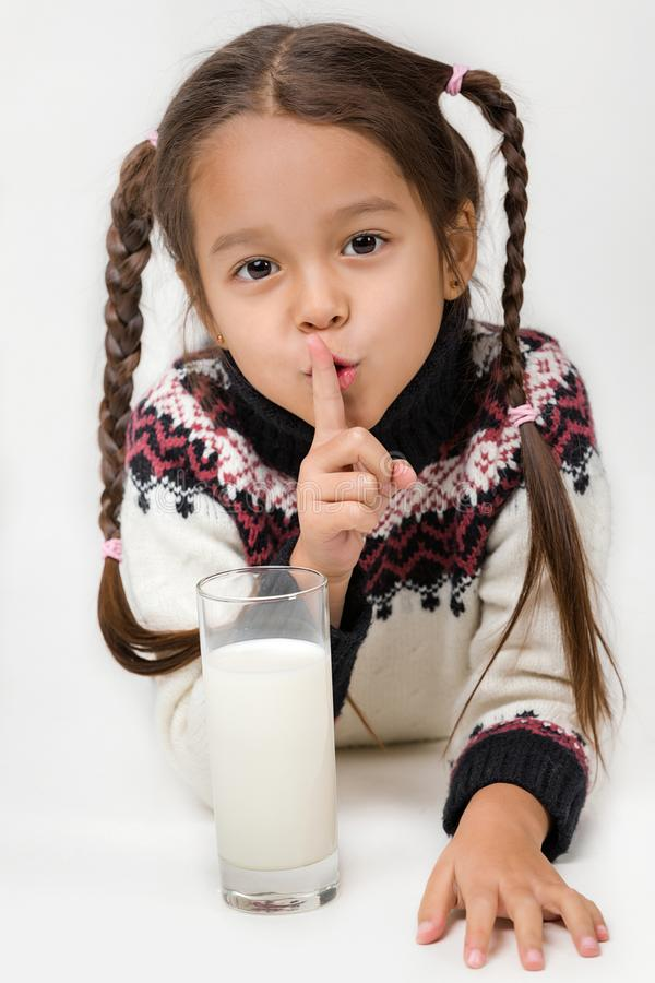 Little child girl holding glass of milk on white background. Portrait of cute little child girl holding glass of milk and showing gesture of quiet royalty free stock images
