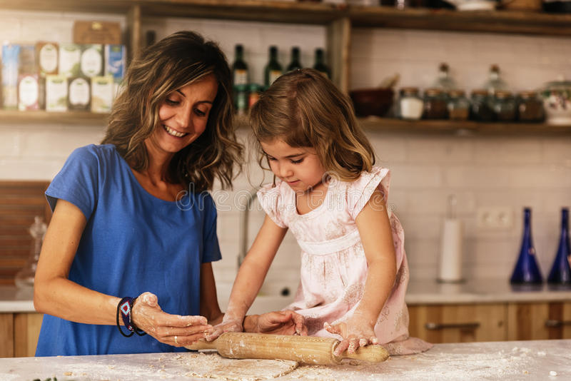 Little child girl kneading dough prepare for baking cookies. royalty free stock image