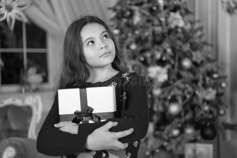 Little child girl likes xmas present. Christmas. Kid enjoy the holiday. Happy new year. small dreaming girl at christmas. The morning before Xmas. New year royalty free stock photos