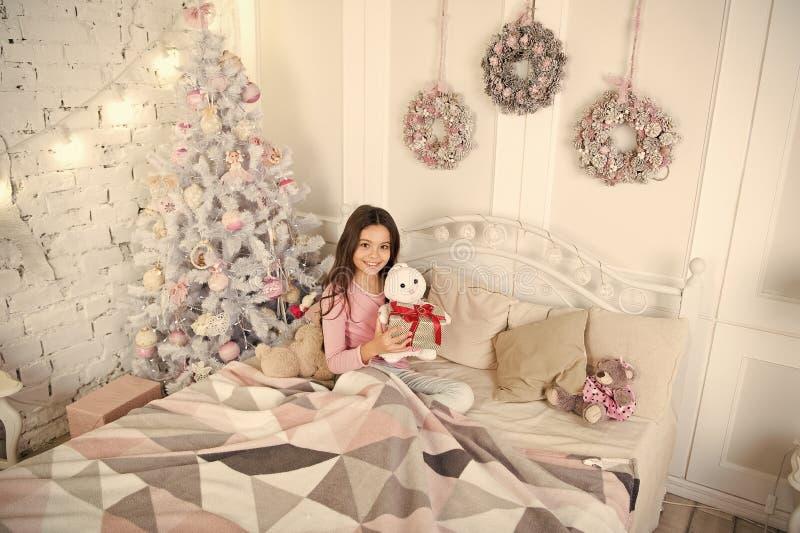 Little child girl likes xmas present. Christmas. Kid enjoy the holiday. Happy new year. small happy girl at christmas. Morning before Xmas. New year holiday royalty free stock photos