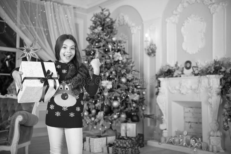 Little child girl likes xmas present. Christmas. Kid enjoy the holiday. Happy new year. small happy girl at christmas. The morning before Xmas. New year royalty free stock photo