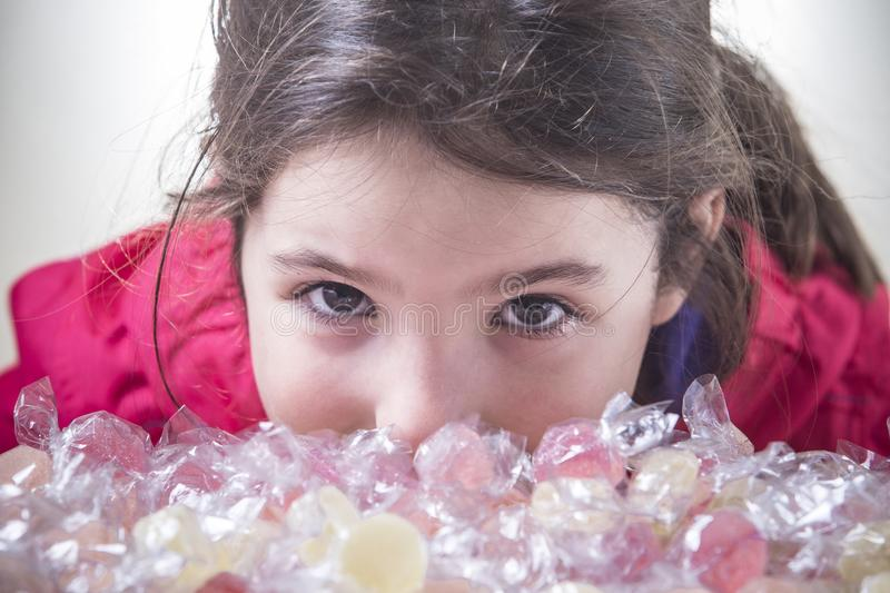 Little child girl look to the camera behind lots of wrapped soft. Jelly gummies. Closeup stock image