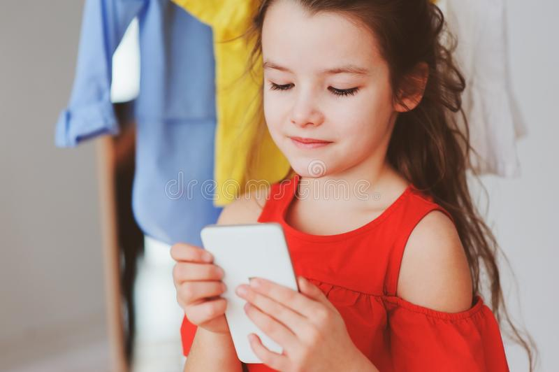 Little child girl making selfie while trying on new clothes in her wardrobe or store fitting room. Kids fashion concept royalty free stock image