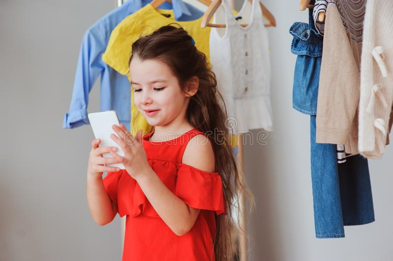 Little child girl making selfie while trying on new clothes in her wardrobe or store fitting room. Kids fashion concept stock photos