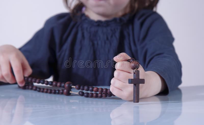 Little child girl praying and holding a wooden rosary as symbol of belief and faith in Jesus Christ and eternal life stock photo