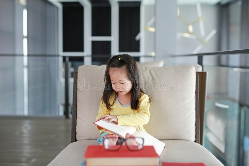 Little child girl reading book in library, Education concept.  royalty free stock photos