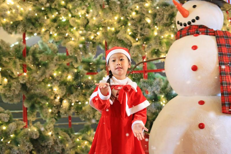 Little child girl in santa costume dress has fun and play with snow on winter time against christmas background. Merry Christmas. And happy new year royalty free stock photo