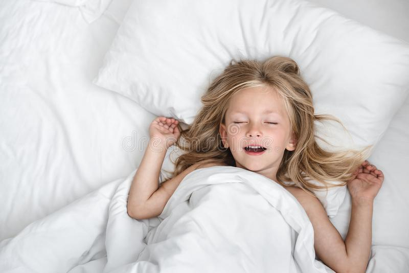 Little child girl sleeping in the bed stock photography