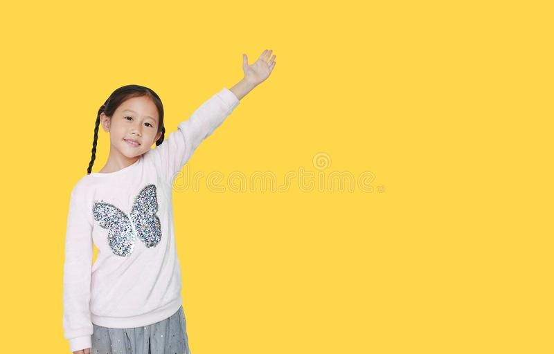 Little child girl standing and points hand up present something isolated on yellow background with copy space. Asian schoolgirl in. Education concept stock photography