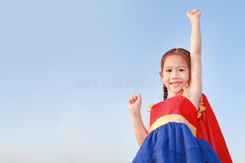 Little child girl Superhero in a gesture to fly on clear blue sky background. Kid super hero concept stock photos