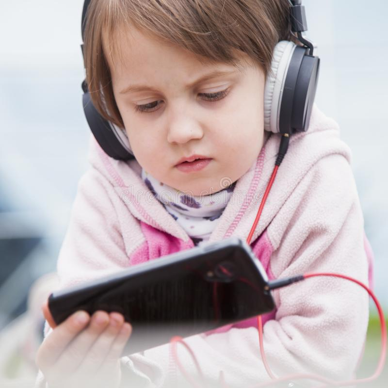 Little child girl using mobile phone watching online e-learning video to studying english royalty free stock image