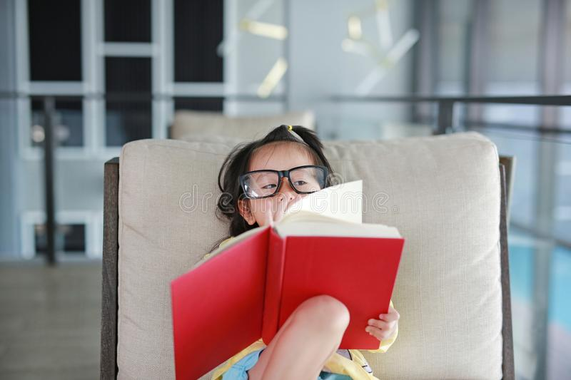 Little child girl wear Glasses reading book in library, Education concept.  stock photo