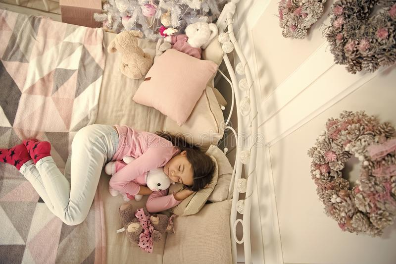 Little child girl with xmas present. happy new year. Christmas shopping. waiting for santa. Winter. small girl sleeping. At home. christmas family holiday. The stock photo