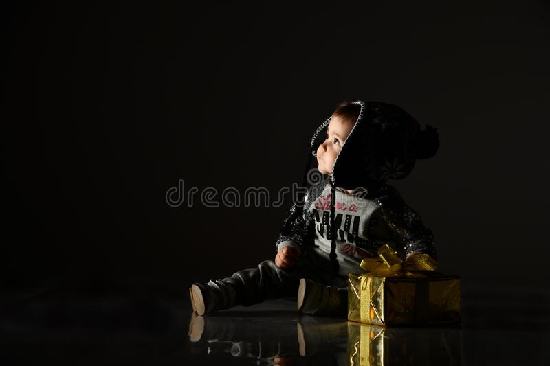 Little child in gray hat, suit and boots. She looking up, holding golden gift box, sitting on floor. Black background. Close up royalty free stock photography