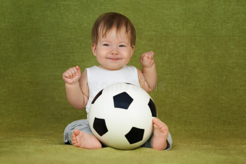 The little child has just got a football ball as a present.  stock photo