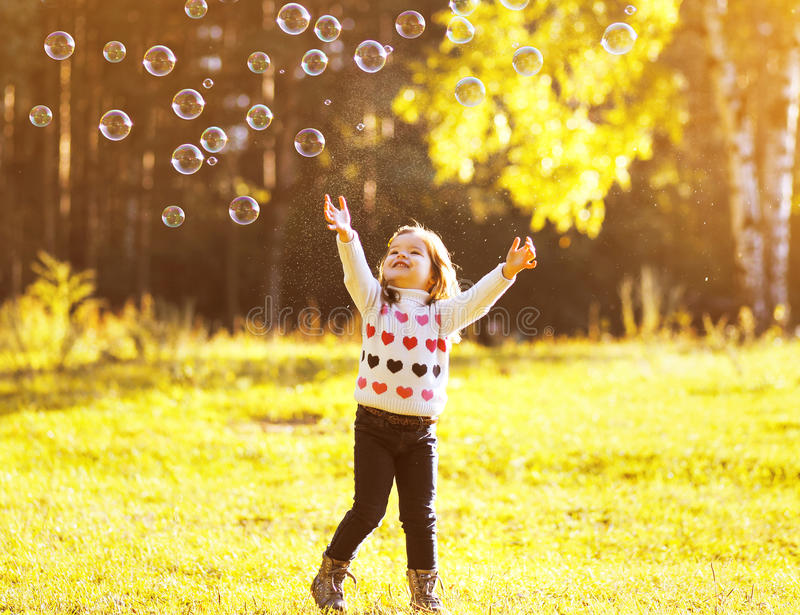 Little child having fun with bubbles soap in sunny autumn day. Outdoors stock photos