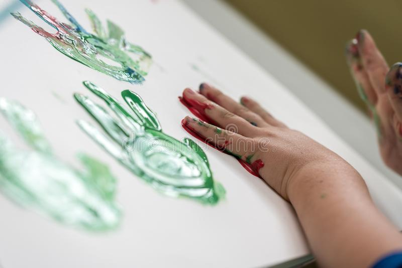 Little child having fun with finger paints stock image