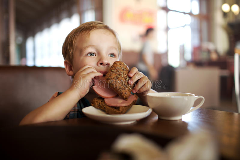 Little child having lunch with sandwich and tea in royalty free stock photo