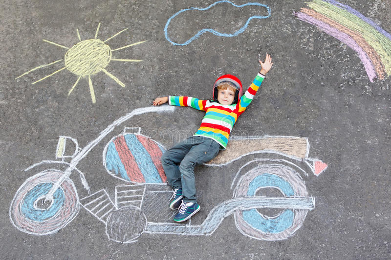 Little child in helmet with motorcycle picture drawing with colo. Creative leisure for children: Adorable little child of four years in helmet having fun with royalty free illustration